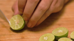 Chef Slices Key Limes on a Bamboo Cutting Board - stock footage
