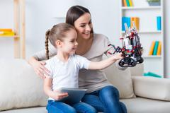 Cheerful mother and daughter playing with robot - stock photo