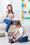 Cute little girl playing with robot Stock Photos