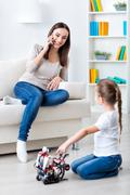 Pretty little girl playing with robot - stock photo