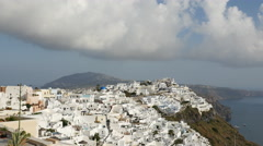 Greece Santorini Fira city under cloud with flying birds Stock Footage