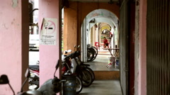 Penang old street sidewalk covered arches with distant woman Stock Footage