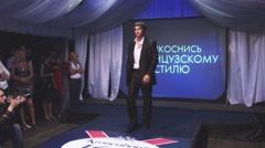 Male model demonstrate business suit on runway in nightclub. Put off jacket - stock footage