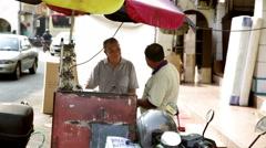 Two Asian men talking under umbrella at street key cutting table Stock Footage