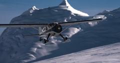 Classic Alaskan Bush Plane Flies Low Over Snowy Ridge with Audio 2K Stock Footage
