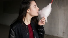 Young brunette woman is eating candy- floss outdoors - stock footage