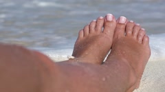 Female toe on sandy beach in caribbean sea waves Stock Footage