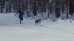 Girl runs with her dog Husky in a winter forest. Arkistovideo