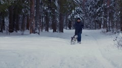 Man runs with the dog Husky in a winter forest towards the camera. Arkistovideo