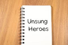 Unsung heroes write on notebook Stock Photos