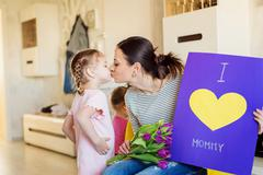 Mothers day, girl giving flowers and card to mom Stock Photos