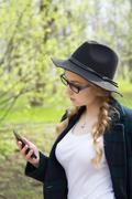 Meditative stylish woman using a mobile phone outdoors in park - stock photo