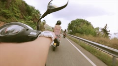 Back side of people in helmets ride on scooters on mountain road. Traveling - stock footage
