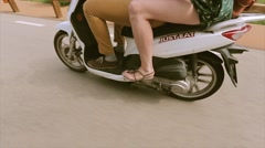 View at feets of girl and boy on driving scooter. Summer sunny day. Traveling Stock Footage
