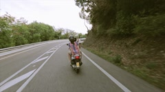 Back side of people in helmets ride on scooters on road. Hilly terrain. Green Stock Footage