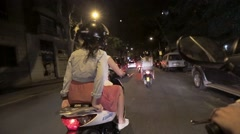Back side girls in helmets ride on scooters in night city. Cars. Traveling - stock footage