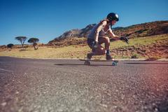 Young woman longboarding on a road - stock photo