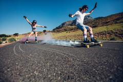 Young people longboarding down the road - stock photo