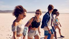Group of young friends walking down a beach Stock Photos
