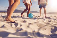 Friends playing soccer on the beach - stock photo