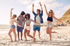 Group of friends having fun at beach - stock photo