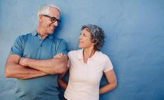 Portrait of affectionate mature couple against a blue wall - stock photo