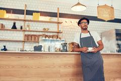 Cafe owner standing at counter with a cup of coffee - stock photo