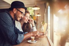 Couple using a digital tablet at coffee shop Stock Photos