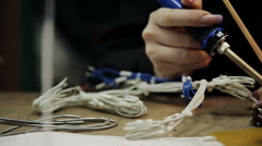 Girl in a repair lab solder the cable to the connector Stock Footage