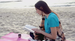 Young Woman Reading a Book on beach drinking hot tea or coffee from thermos Stock Footage