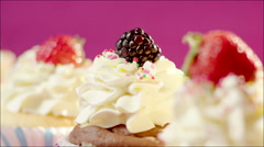 Tasty home-made cup-cakes with berries on the table - stock footage