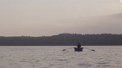 Man rowing on a calm wild lake Stock Footage