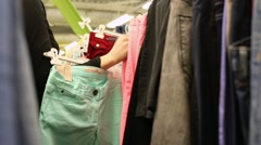 Female Hands Plucked Jeans On Hangers Stock Footage
