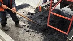Workers with shovels repairing asphalt. - stock footage
