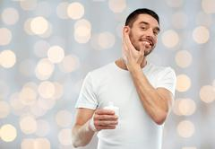 Happy young man applying cream or lotion to face Stock Photos