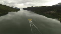 AERIAL CHASE SHOT OF FLOAT PLANE TAKE OFF IN LAKE BC CANADA - stock footage