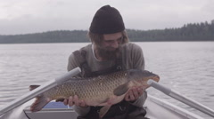Fisherman holding a carp in his hand - stock footage