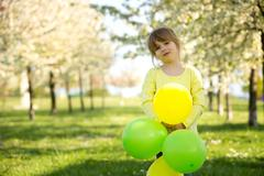 Cute little girl playing with balloons in a blooming apple tree garden Stock Photos