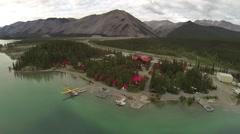 BEAUTIFUL AERIAL FLY OVER CAMP SITE NEXT TO LAKE AND MOUNTAINS Stock Footage