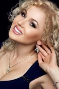 Studio portrait of gorgeous blonde woman smiling, darling necklace on her neck - stock photo