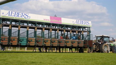 4k Horse Racing low angle jockeys horses enter start boxes Stock Footage