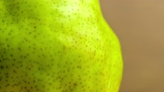Macro of bright green pear as water sprinkles against it, wetting the fruit. Stock Footage