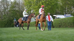 4k Horse Racing horses and jockeys guided to the course Stock Footage