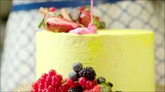 Pink cream sprinkling down tasty birthday cake - stock footage