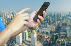 Hand of Young adult Tourist use Mobile Device smartphone over City Building B Kuvituskuvat