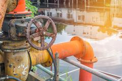 Valve of water pipe for pump system in canal Stock Photos
