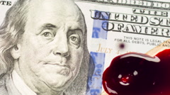 Droplets of blood landing on one hundred dollar bill slow motion Stock Footage