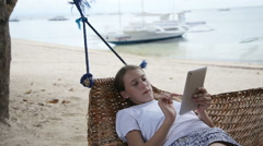 Girl in the hammock with the tablet on the beach - stock footage