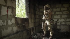 Soldier in the burned a room aiming a machine gun and looking through binoculars - stock footage