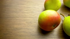 Panning overhead shot of fresh red and green pear fruits scattered on wooden  Stock Footage